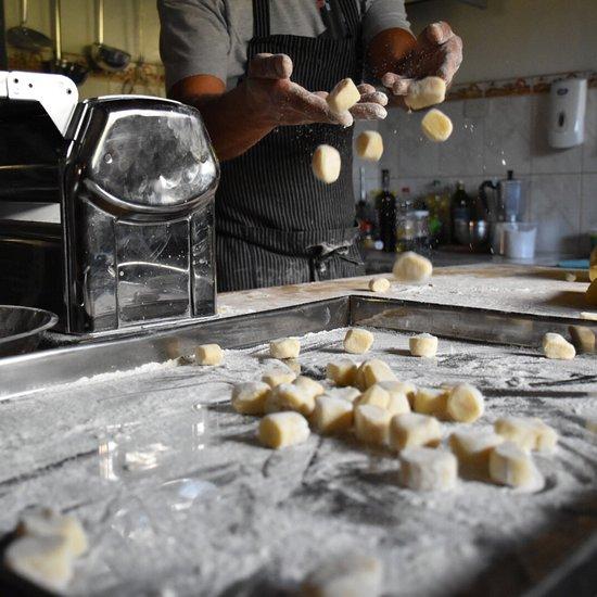 A chef preparing some dough in the kitchen at Antica Osteria.