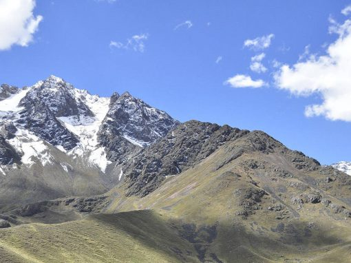Landscape of snow-covered mountains and yellow-green hills in the Peruvian Andes Mountains.