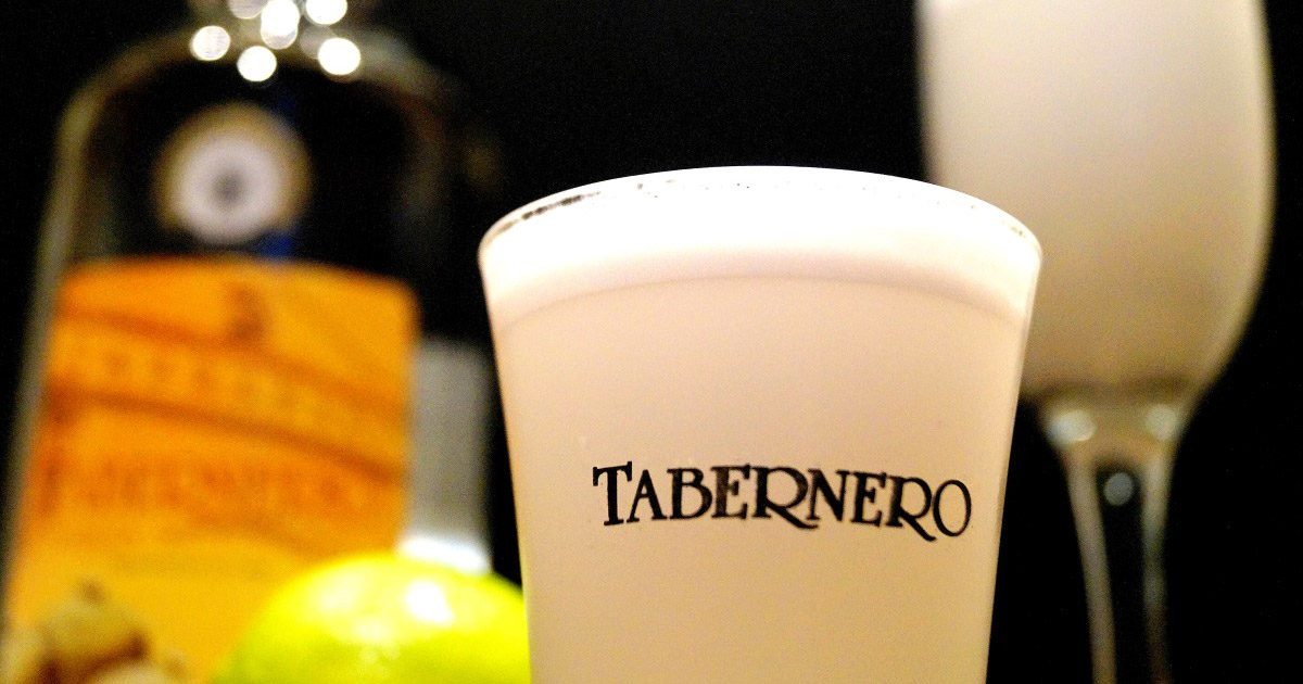 A cup of pisco sour labeled Tabernero with a bottle, some limes and another glass behind.