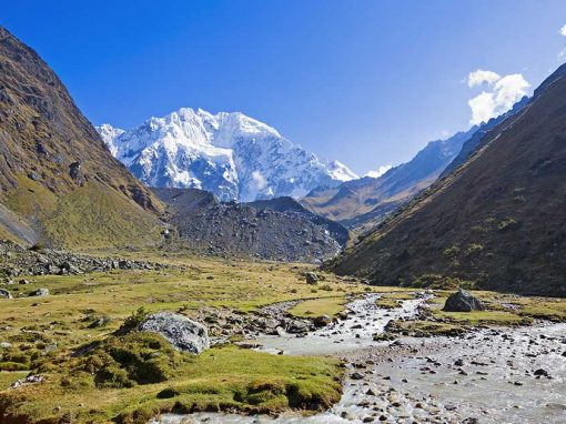 Snow-capped peaks across a green valley with blue skies along the Salkantay trek.