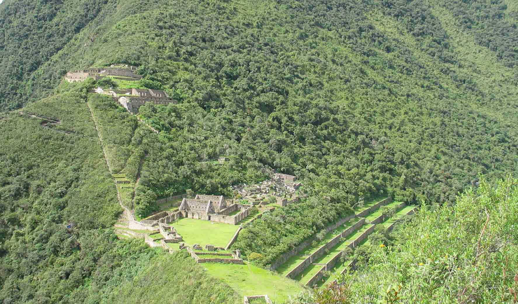 Choquequirao ruins from afar. Several levels of stone buildings with surrounding lush greenery on a mountainside.