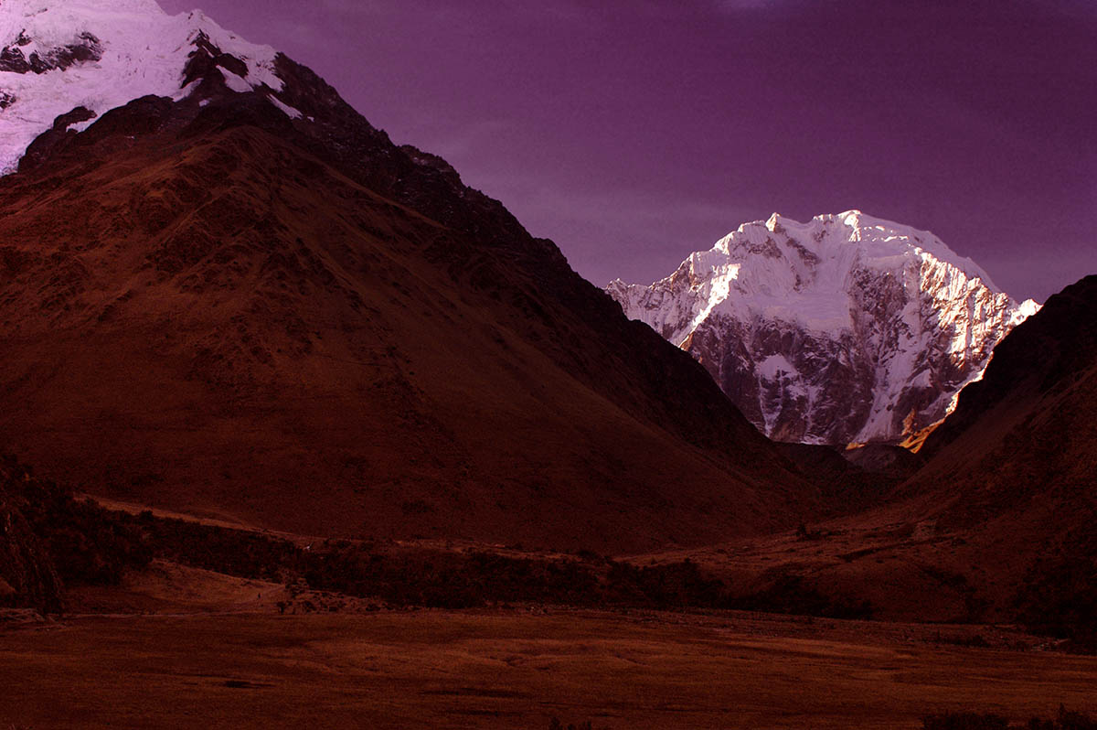 Red tinted ground with snow covered mountains in the distance and a purple tinted sky.