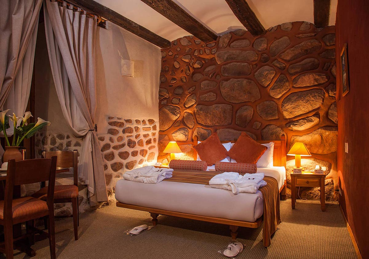 Guest room at Hotel Monasterio de la Recoleta, with Andean textile, stone accents and exposed wood