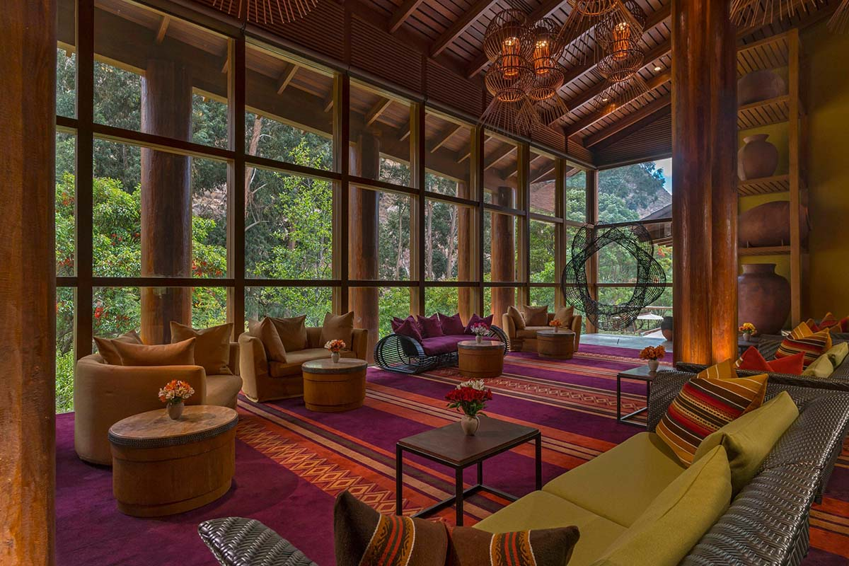 Andean textiles, floor-to-ceiling windows and green mountains beyond at Tambo del Inka hotel.