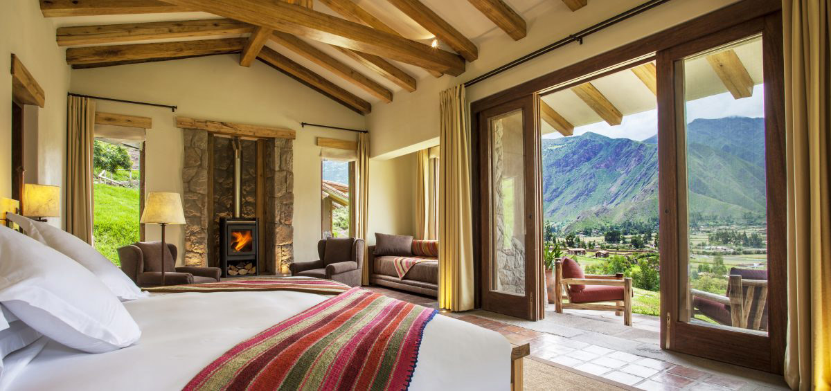 Room at Hacienda Urubamba, with exposed wood, Andean textiles and mountain views out a sliding door.