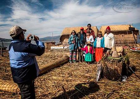 tourists and Uros family pose for photos