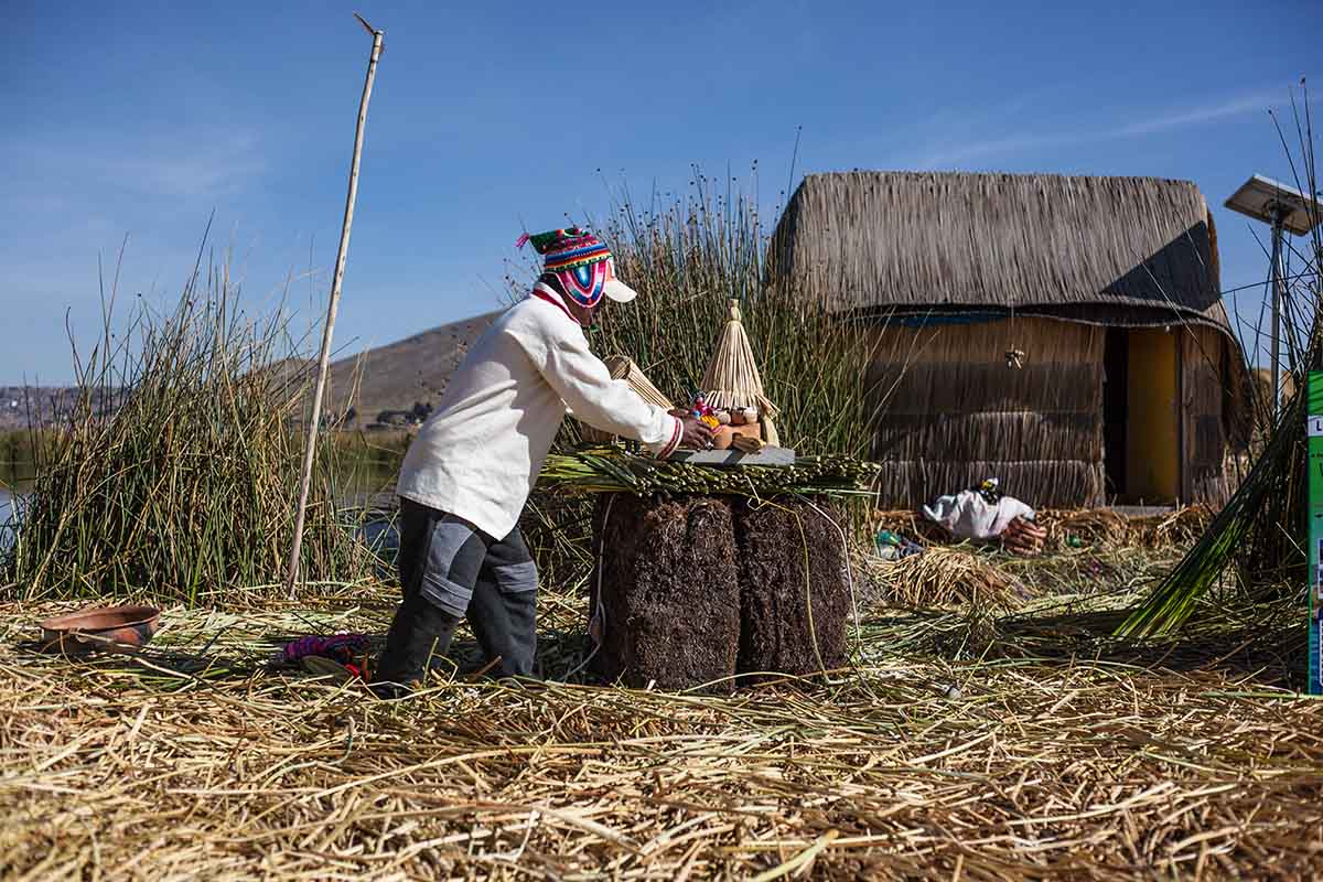 Man standing on a reed ground demonstrating how the Uros Islands are constructed. Reed house in background.