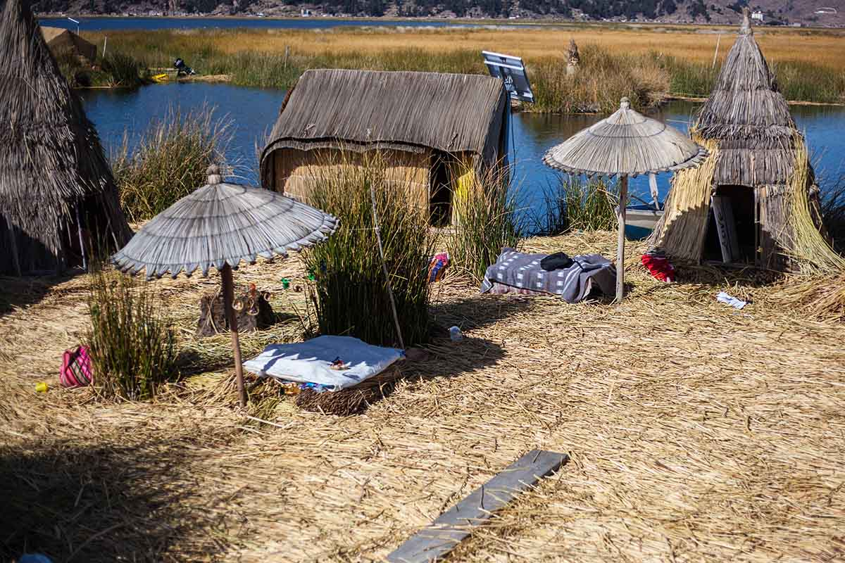 High angle view of an Uros Island with reed houses and umbrellas in view.