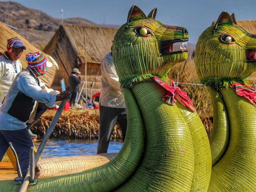 Three Uros Islanders manning a green reed boat with two heads in the shape of pumas.