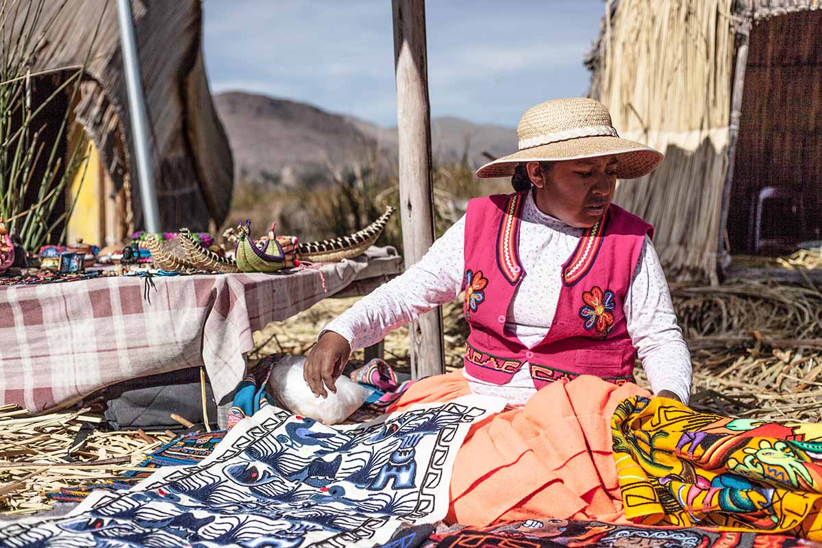Uros woman in traditional dress with handicrafts.