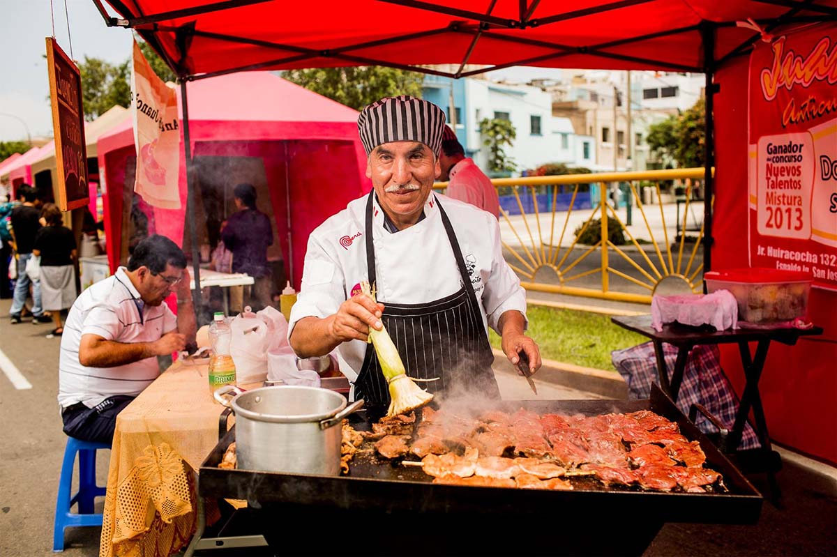 Man in chef's outfit and apron making anticuchos at the famous Mistura Food Festival in Lima, Peru