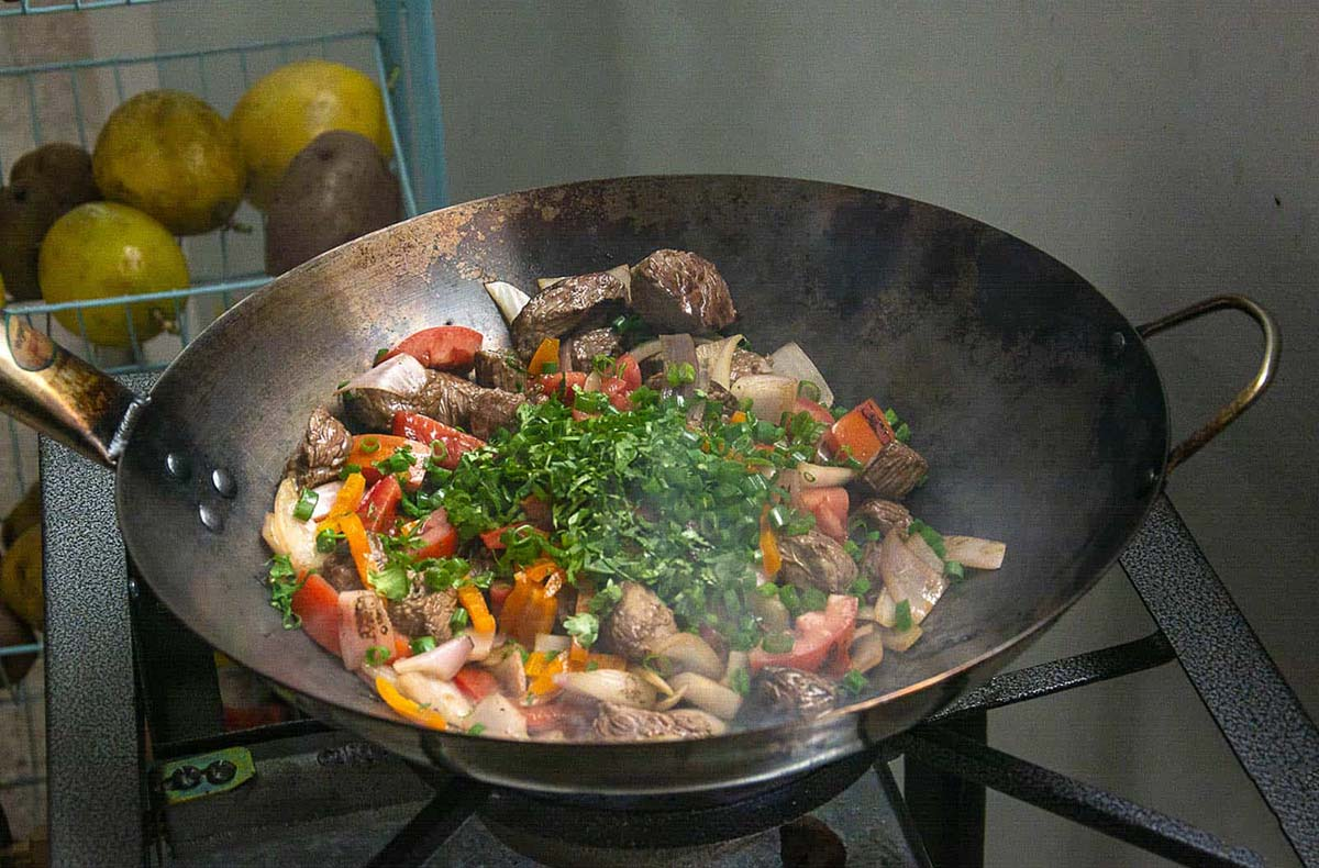 Peruvian lomo saltado being prepared in large pan as part of Exquisito's cooking class, a popular lima tour option for foodies