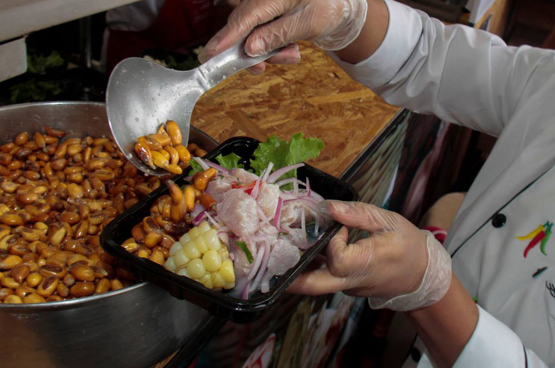 Peruvian ceviche being served up with a side of chocolo and canchita at the Mistura Food Festival, a popular gaastronomic event in Lima