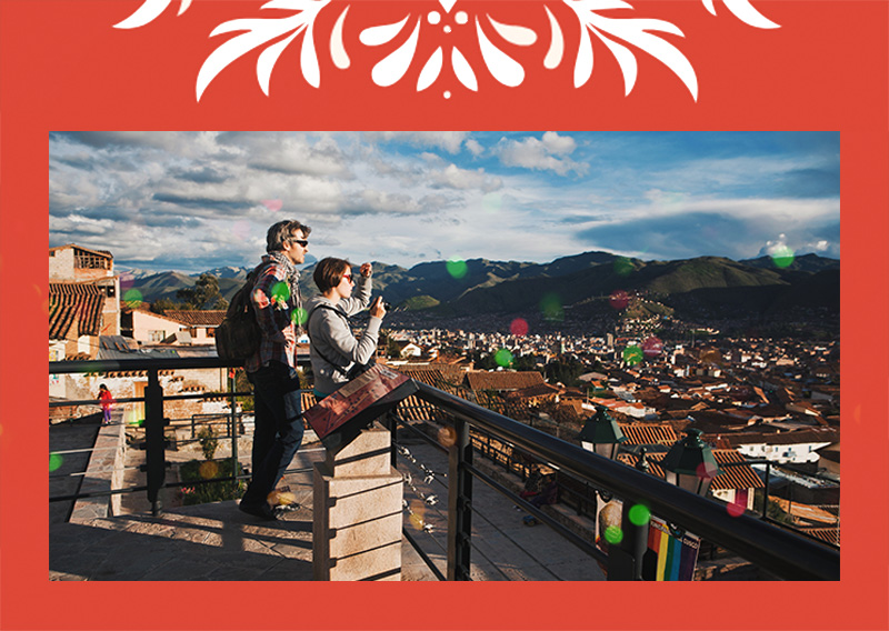 A couple looking at a panoramic view of Cusco city , with a holiday frame around the image