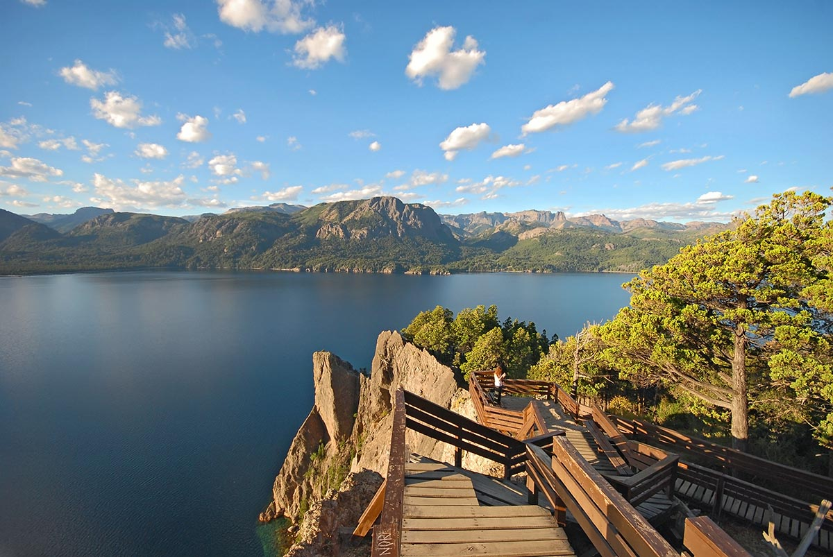 A deep blue lake with a wooden hiking path along the shore in the Nahuel Huapi National Park.