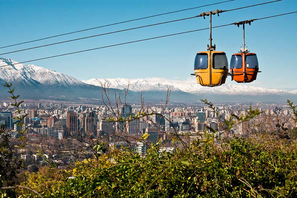 Two cable cars cross paths with Santiago, Chile and the surrounding mountain landscape behind.