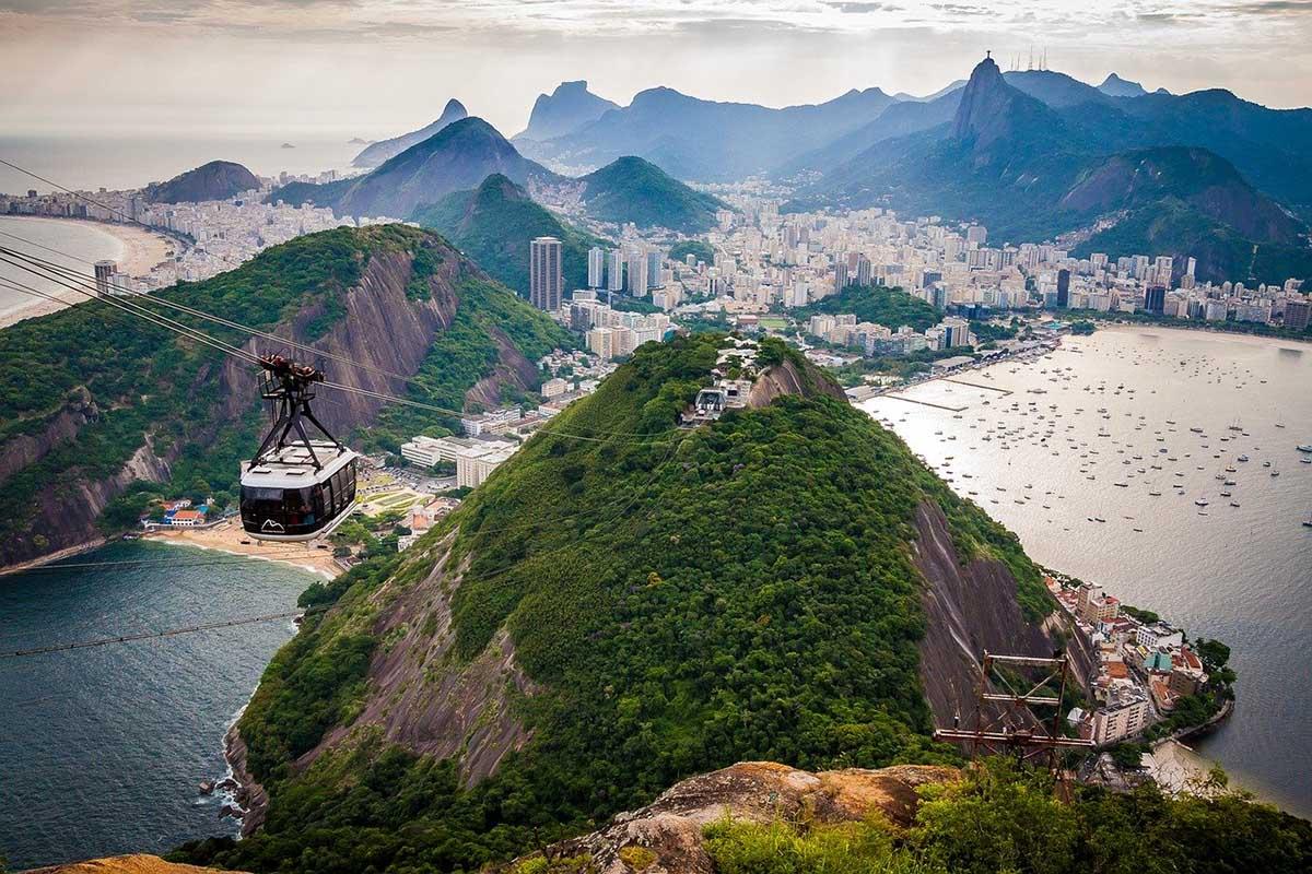 Cable cars in Rio de Janeiro pass through a green mountainous landscape along the ocean.