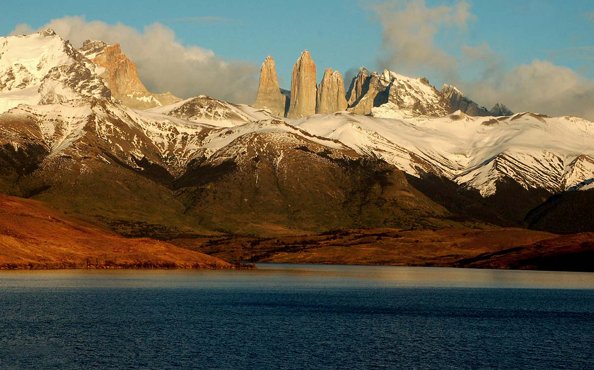 Granite spires, snow covered mountains, and a deep blue lake in the Torres del Paine National Park.