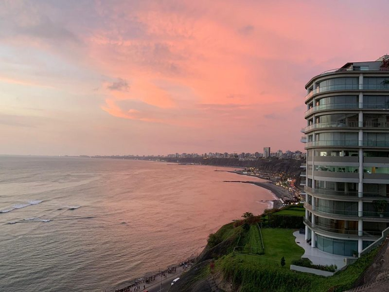 Pink hues in the sky and ocean at sunset in Barranco. Several tall buildings sit along the coast.