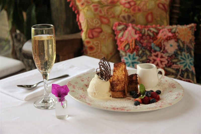 Glass of sparkling wine and plate of ice cream, French toast and fruit sit on a white linen table.