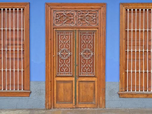 Two wooden windows, a wooden door, and blue wall. Colonial metal designs covering the door and metal bars on windows.