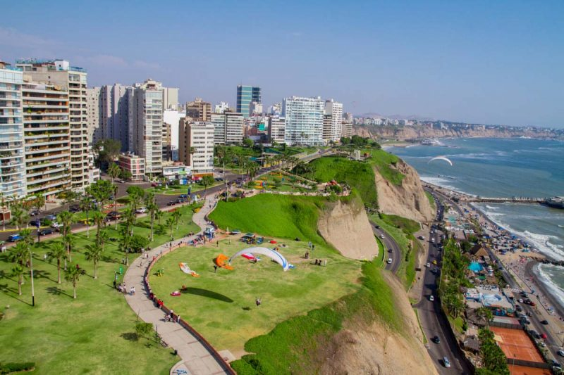 Aerial view of tall buildings, several roads, green parks, and the ocean in Miraflores, Lima.