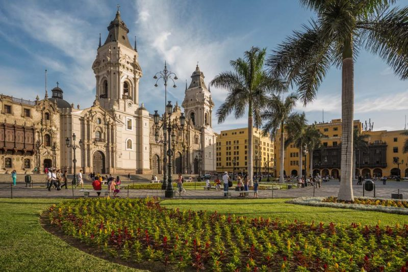 Lima's Plaza de Armas, the Archbishop's Palace and Cathedral with grass, flowers and palm trees.