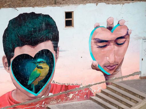 A mural in Barranco of a man removing a heart-shaped piece of his face to reveal a bird underneath.
