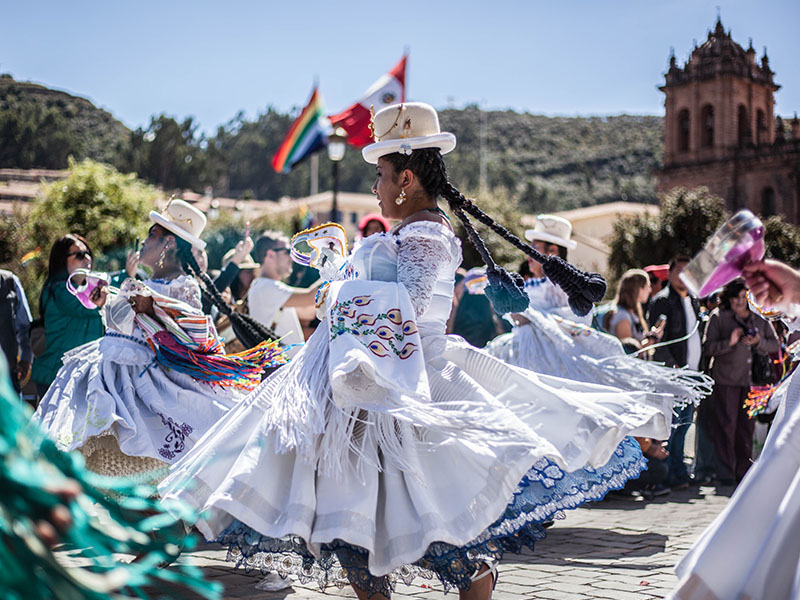 Women with braids wearing traditional dresses and dancing at the Inti Raymi festival in Cusco.