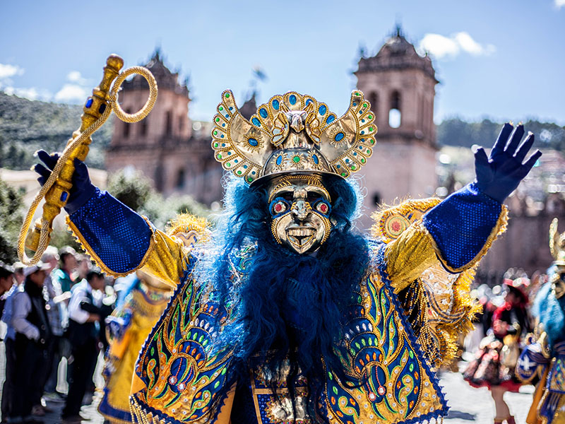 A performer wearing a bright yellow and blue costume at the Inti Raymi festival in Cusco.