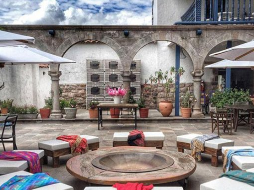 A table and benches in the courtyard of El Mercado Boutique Hotel in Cusco.