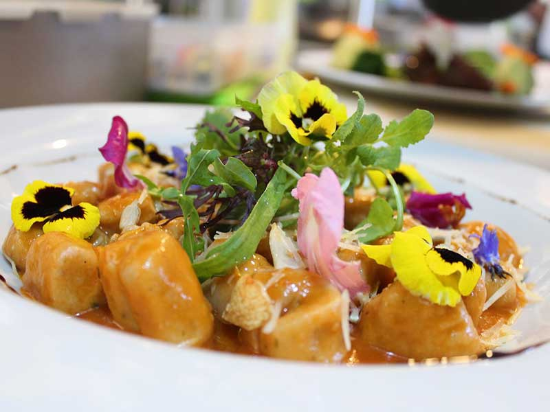 colorful food dish topped with lettuce and edible flowers