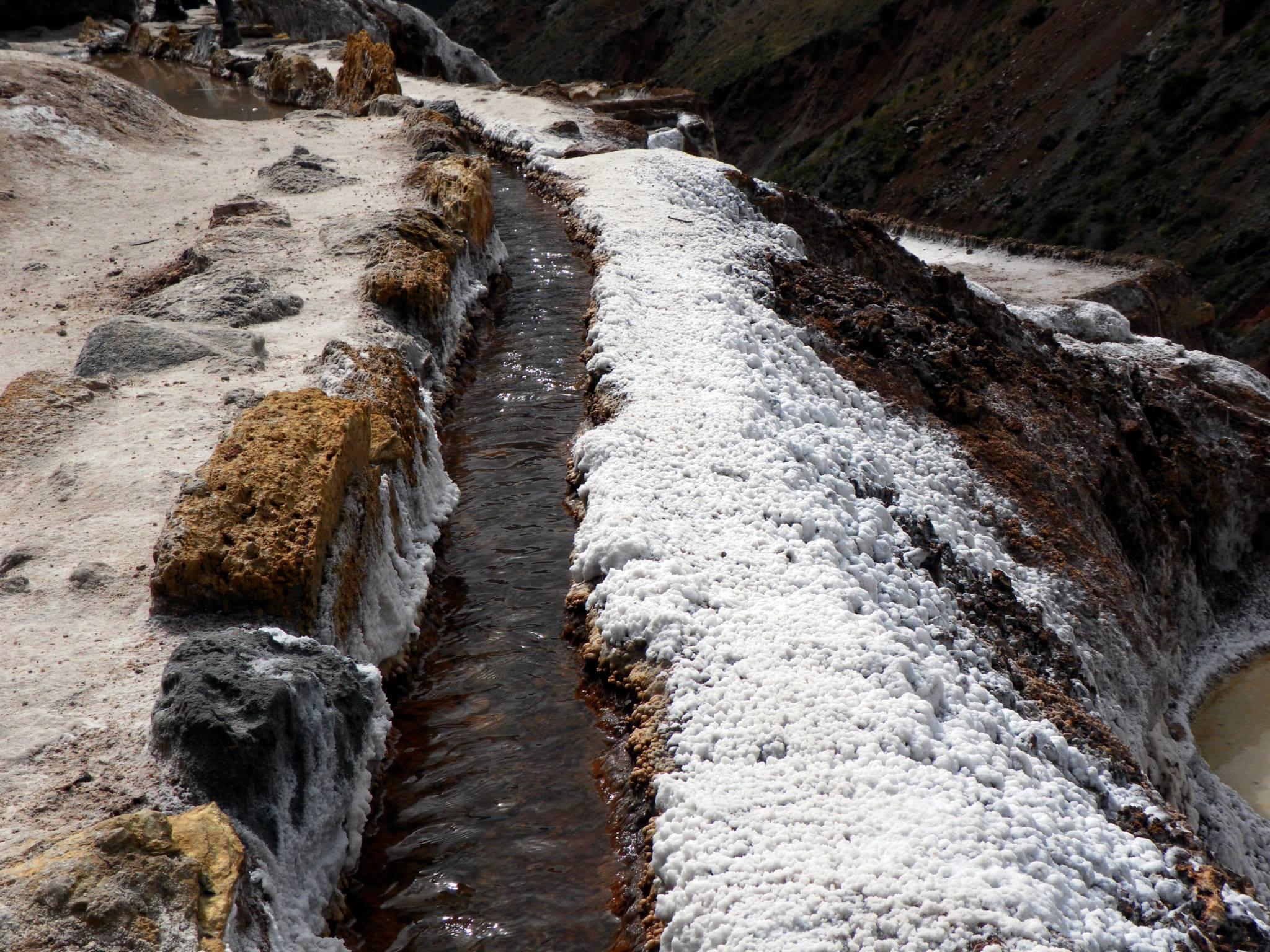 A canal of water running through the salt pans of Maras.
