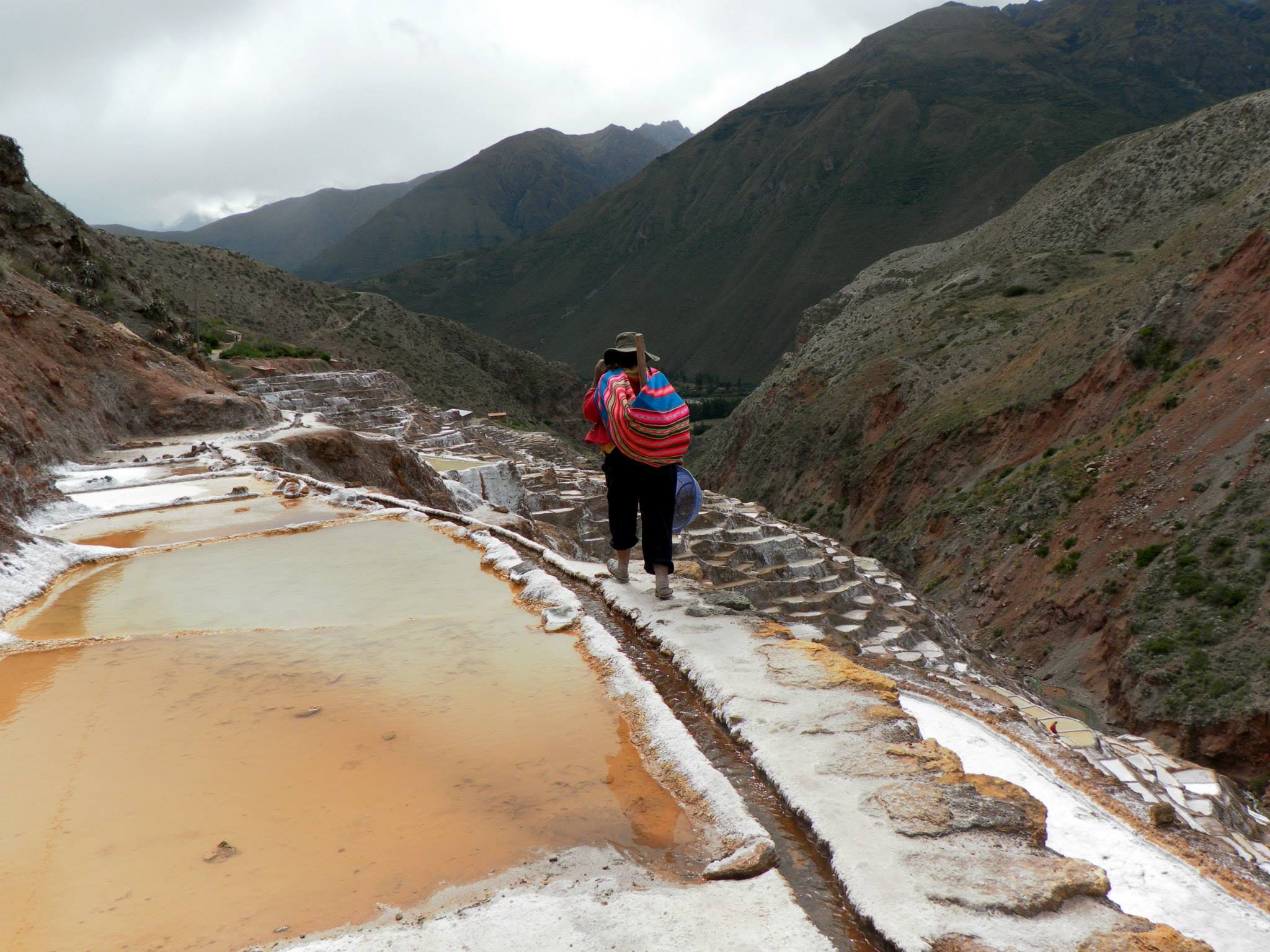 Person with colorful Andean pack full of supplies to start working in the Salt Pans.