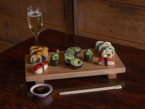 Vegan sushi dish and a glass of champagne at El Buda Profano in Arequipa
