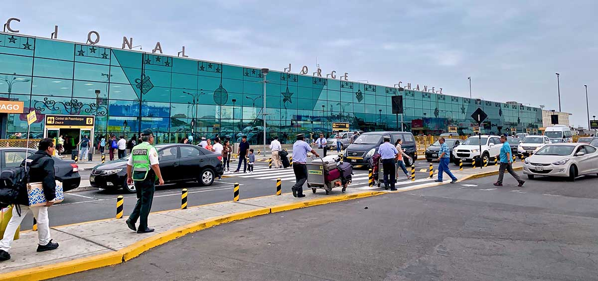 Many people walking and cars driving in front of the Lima airport.