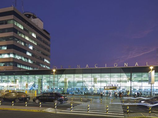 Front of the Lima airport with cars in front and purple night sky in background.