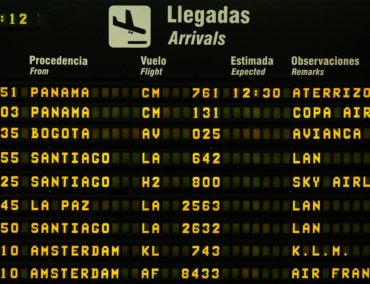 Black board with white and yellow writing listing the arrival of international flights.