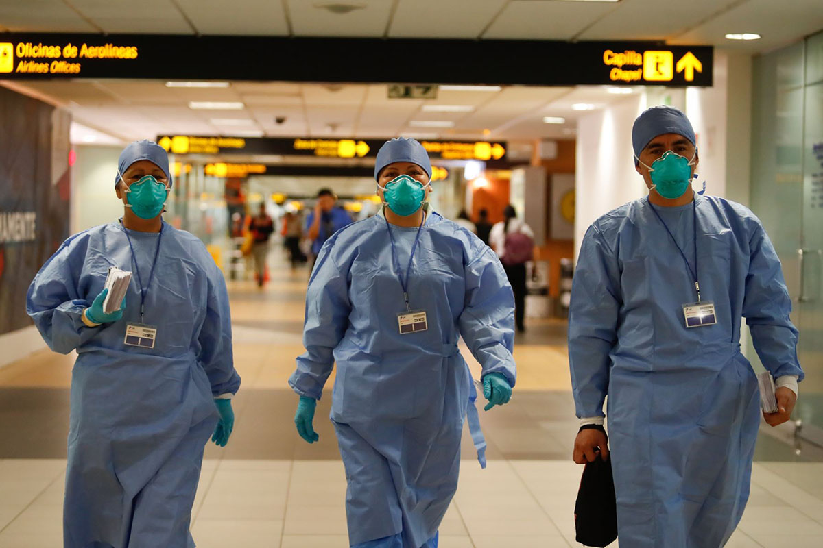 Three doctors walking in the Lima airport using blue medical caps, masks, gloves, and clothing.