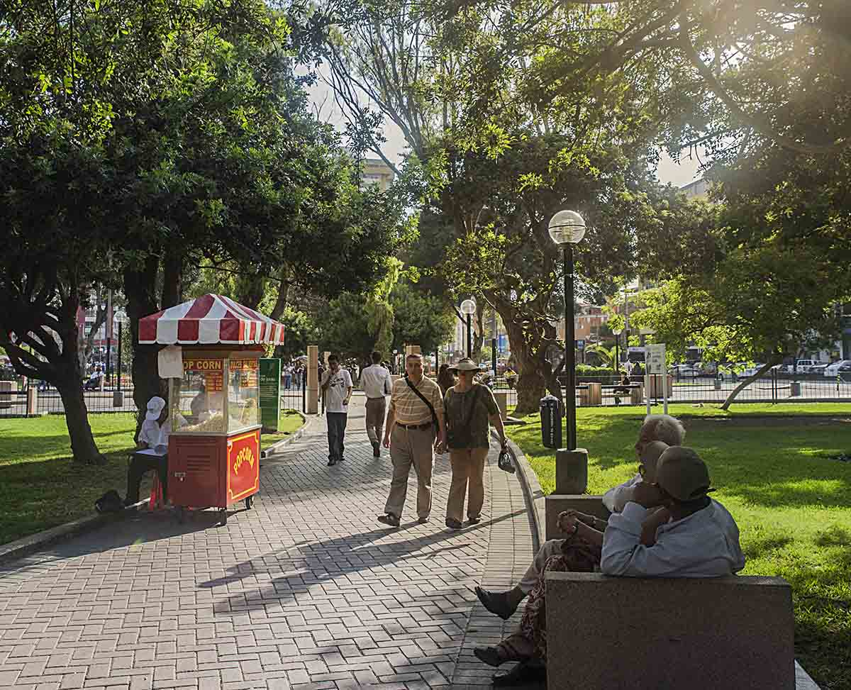 People walking through Parque Kennedy, passing a popcorn vendor and people sitting on benches.