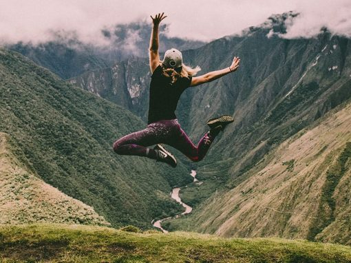 A female tourist jumping into the air at Machu Picchu with the Urubamba River as a backdrop.