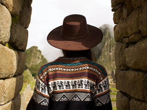 A woman wearing an alpaca sweater looking through a stone doorway at the ruins of Machu Picchu.
