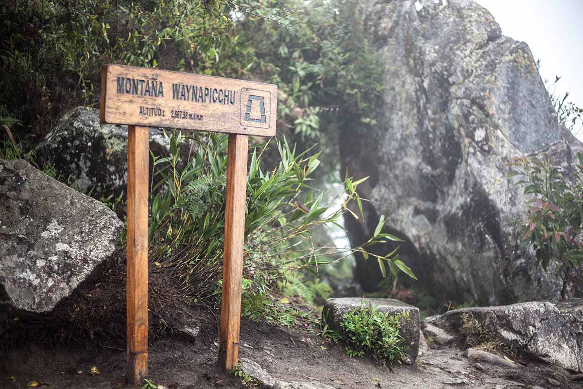 """A wooden sign at the top of Huayna Picchu mountain says, """"Montaña Waynapicchu"""" and the altitude."""