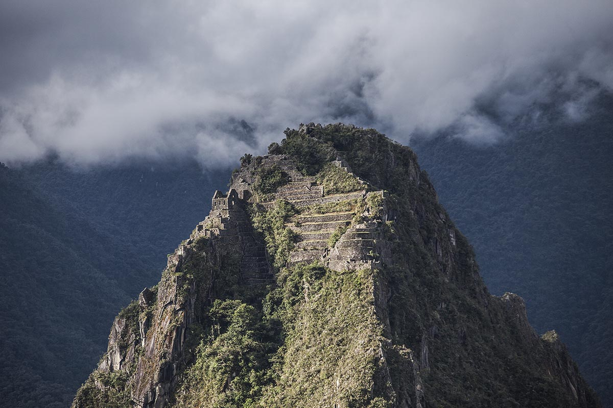Stone ruins atop the Huayna Picchu peak pierce the clouds above.