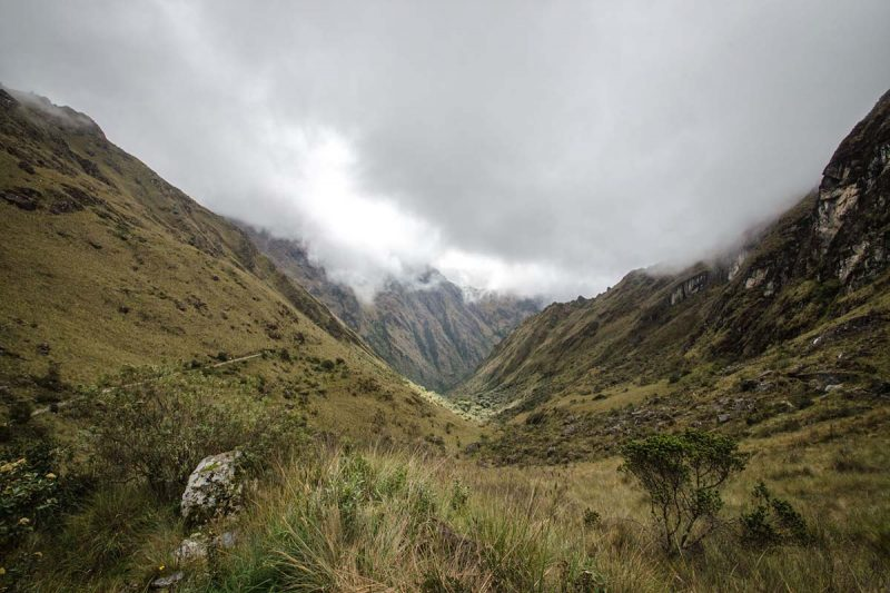 Grey clouds above yellow-green terrain at Dead Woman's Pass.