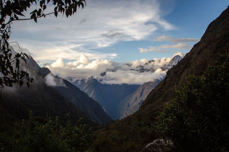 View of mountains, clouds, and blue skies in the distance at an opening between two mountains.
