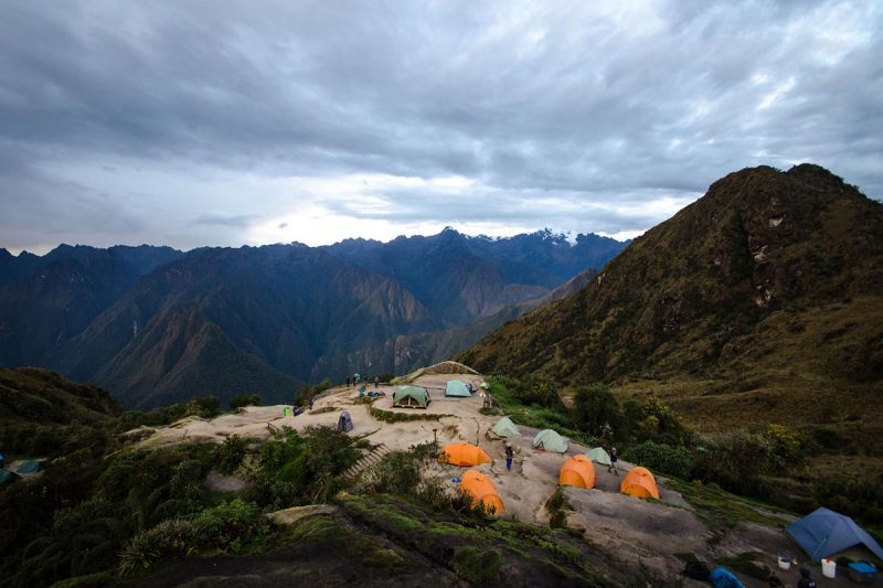 High angle over Winaywayna campsite with multicolored tents and mountainous terrain in background.