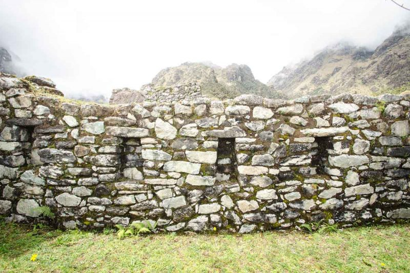 Stone patchwork wall of the Conchamarca ruin with four rectangular cutouts.