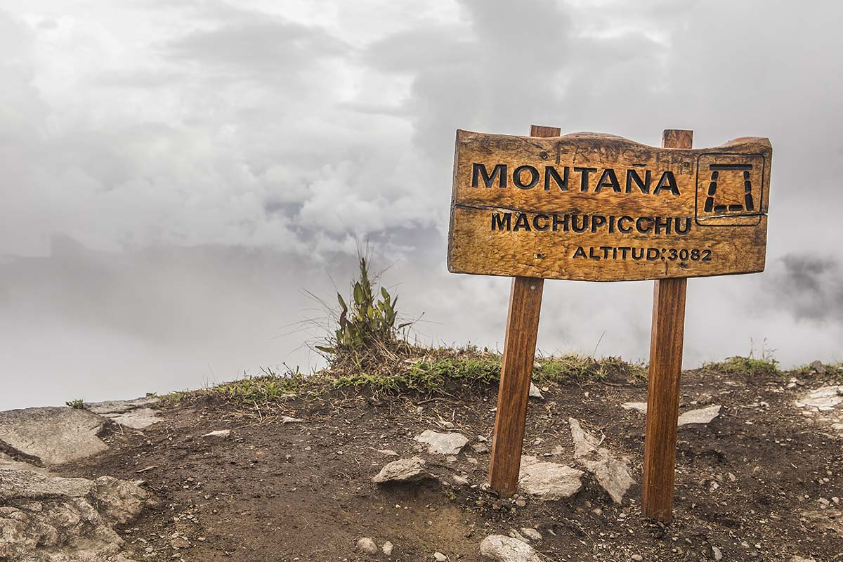 """The wooden sign places atop Machu Picchu Mountain, stating """"Montaña Machupicchu"""" and the altitude: 3,082 meters, or 10,111 feet, above sea level."""
