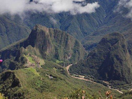 Aerial view of Machu Picchu stone ruins surrounded by green mountains and clouds.
